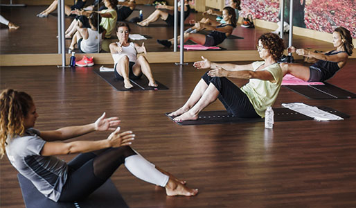 Image of a group of 3 ladies doing yoga in a mirrored studio
