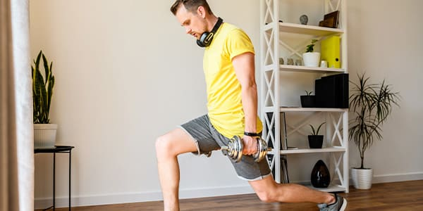 Image of man doing lunge during home workout