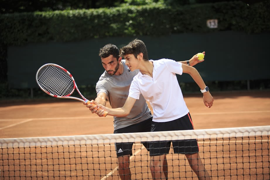 A tennis coach teaches a pair of children to improve their tennis
