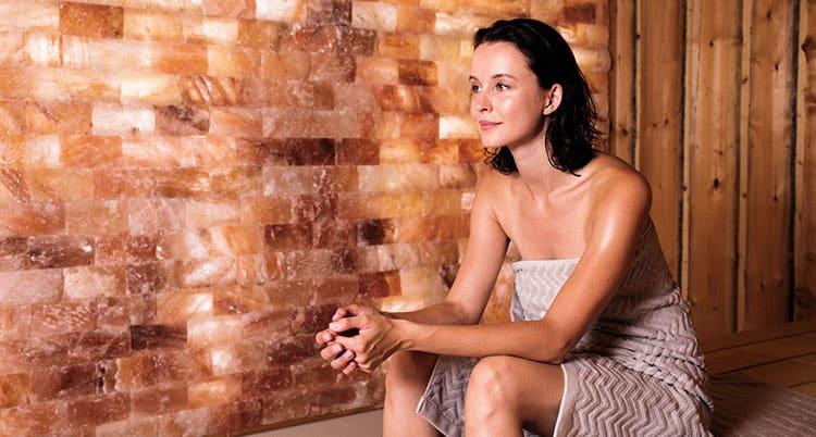 Eine Frau sitzt in einer Salzkristallsauna