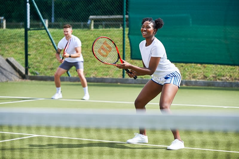 Members playing tennis outdoors