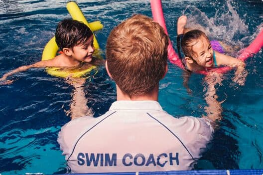 A pair of kids and pool noodles learning from one of our expert swim coaches