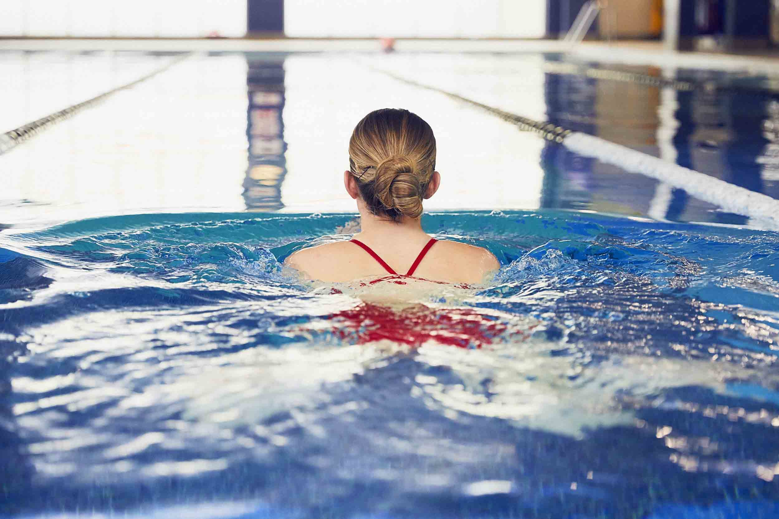 Woman swimming in an indoor pool.