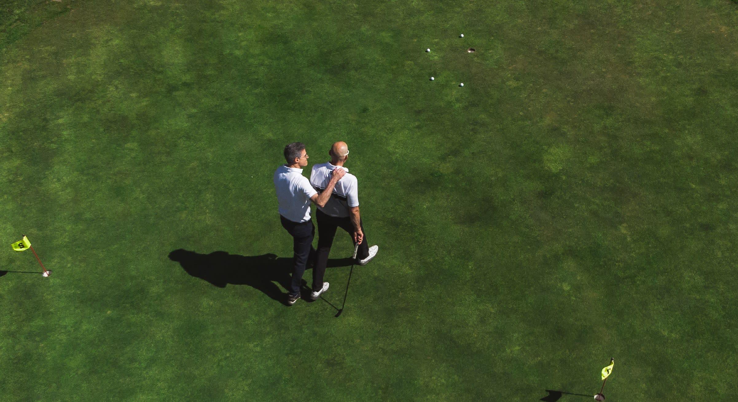 Deux hommes qui se discutent sur le green de golf.