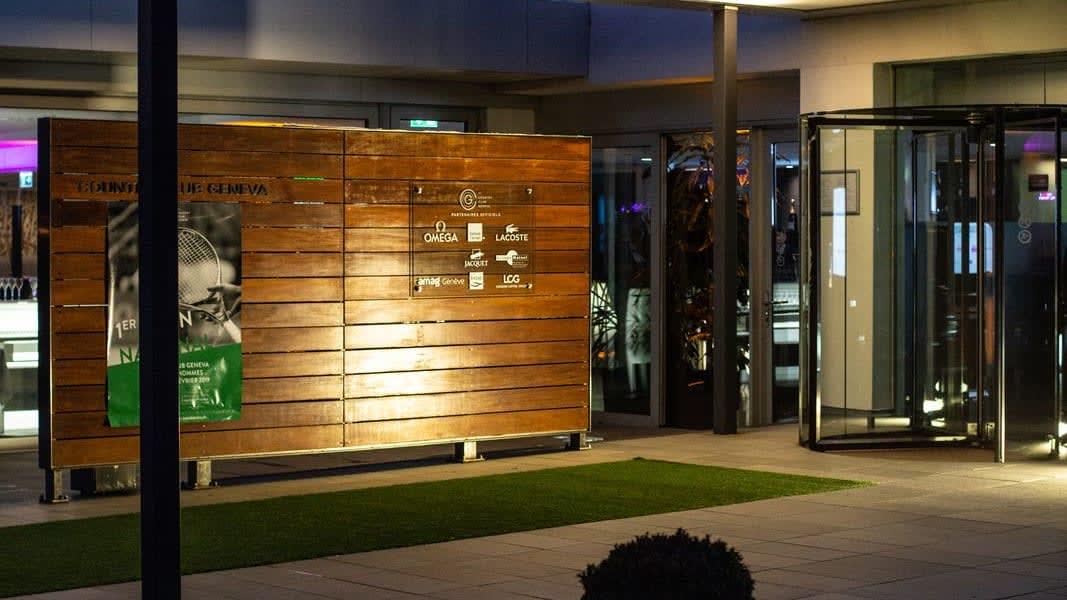 L'entrée du Country Club Geneva avec les noms des sponsors sur le mur menant à l'entrée.