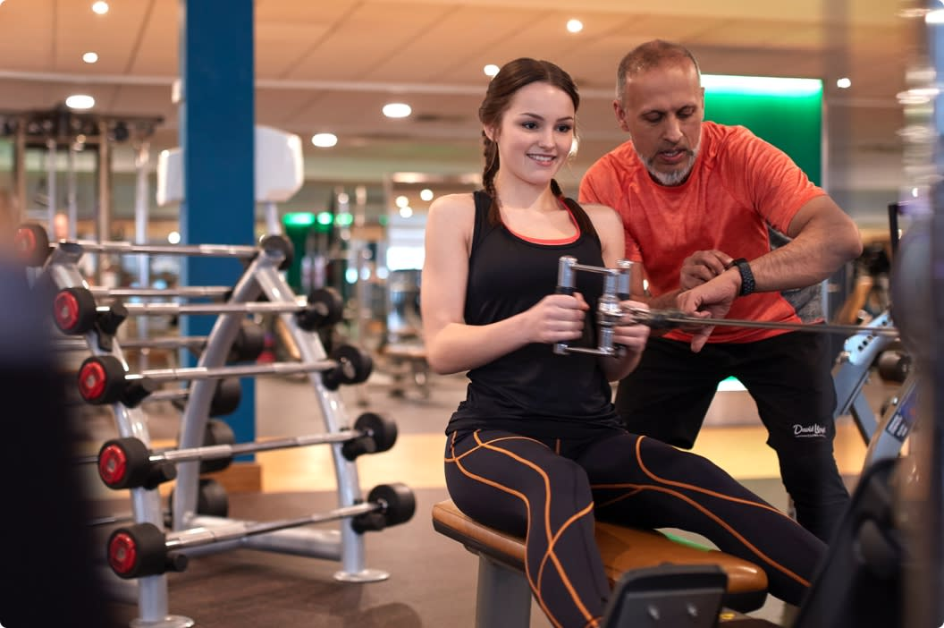 A personal trainer works with their client