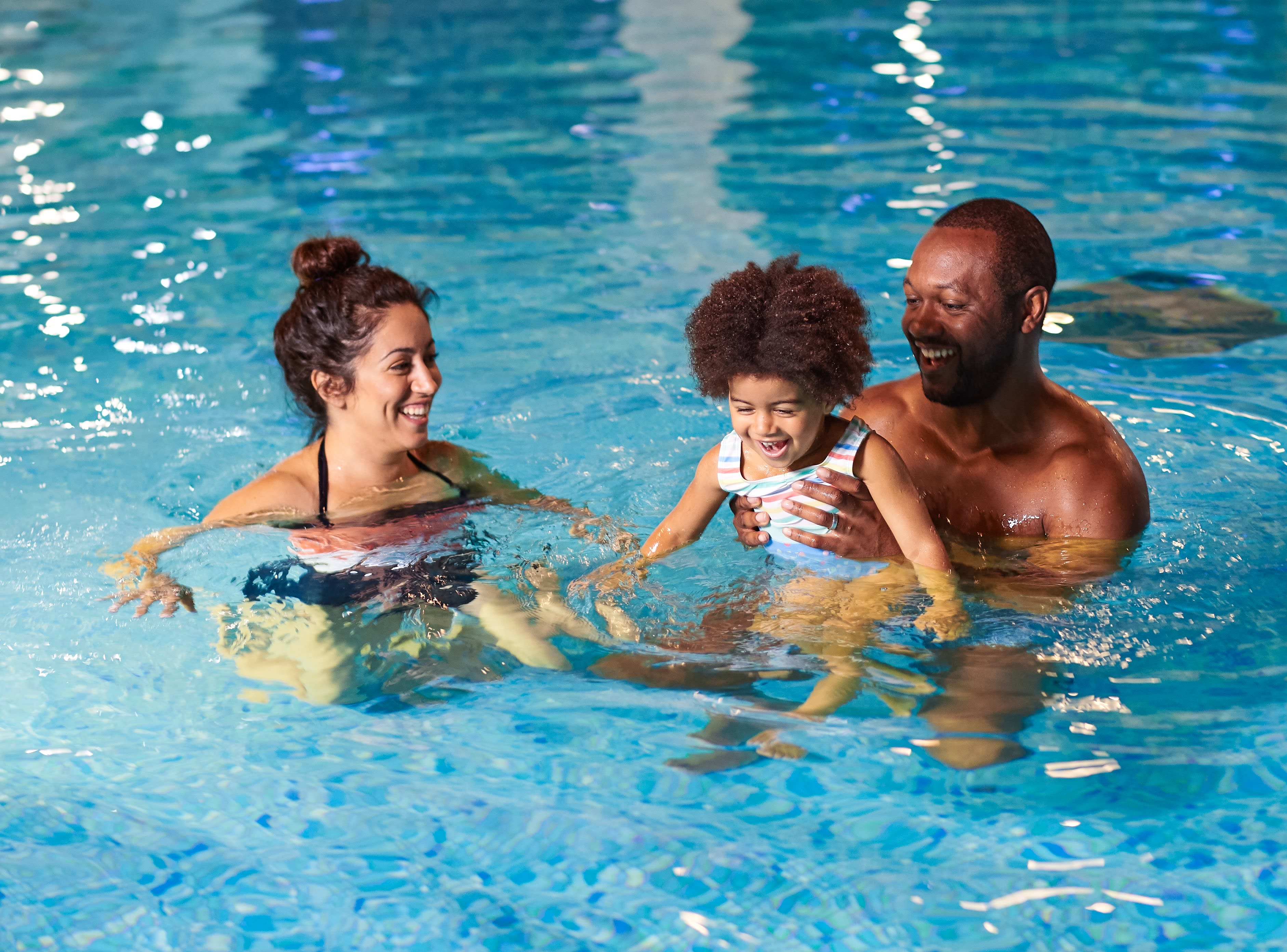 A grinning family playing in the pool