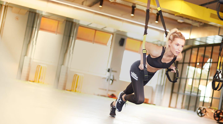 Frau trainiert an TRX-Bändern