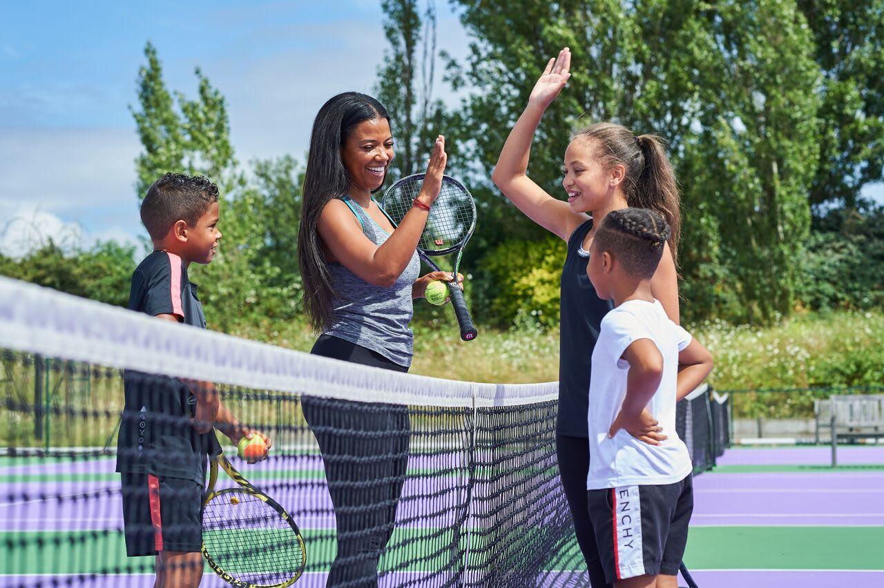 A tennis coach helps a member improve her technique