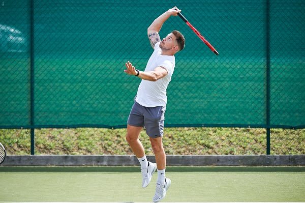 Image of man hitting serve on outdoor tennis court