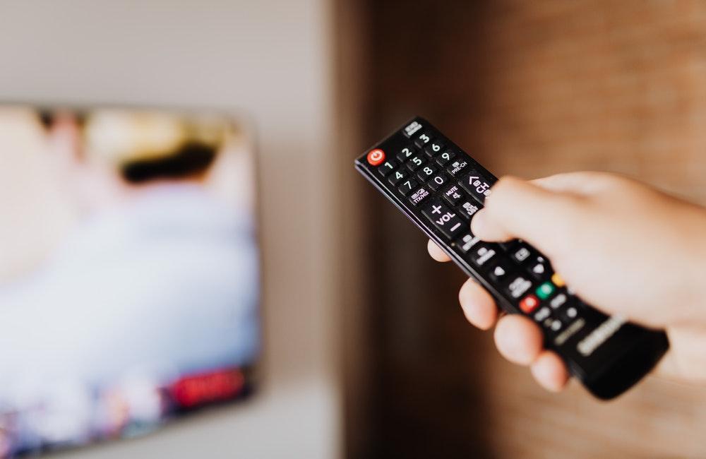 Image of person pressing TV remote