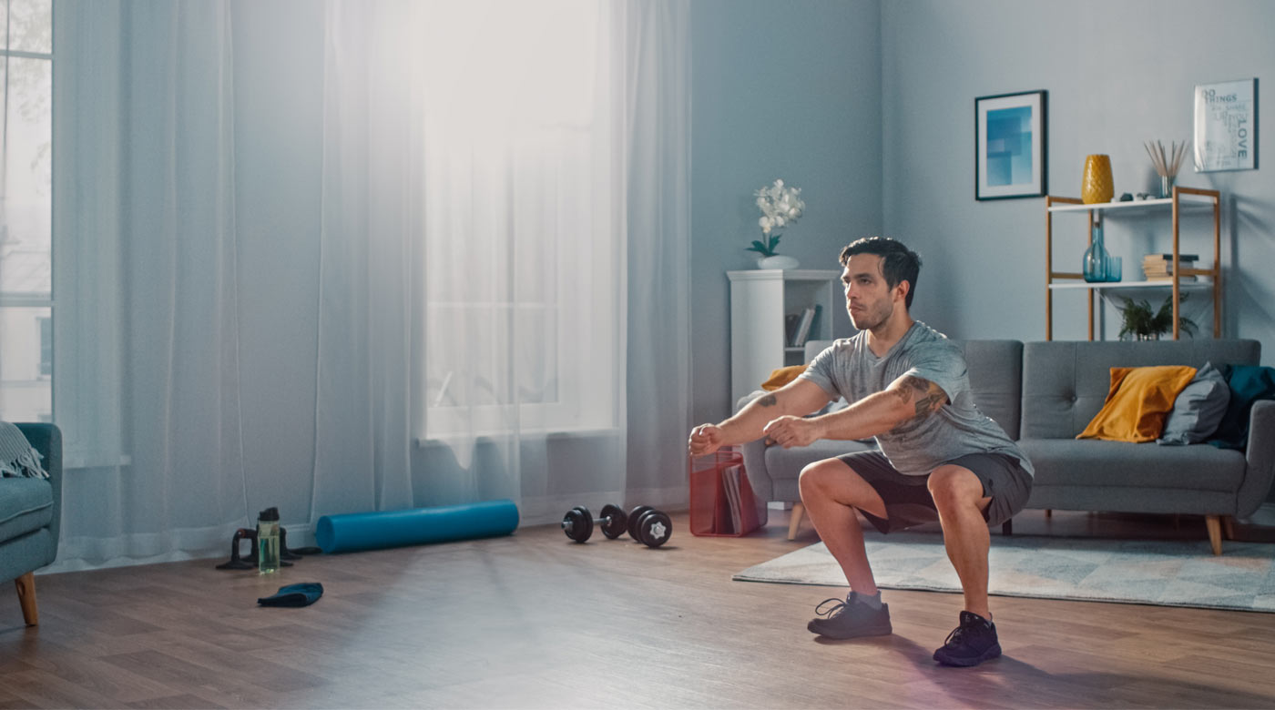 Image of man squatting during home workout