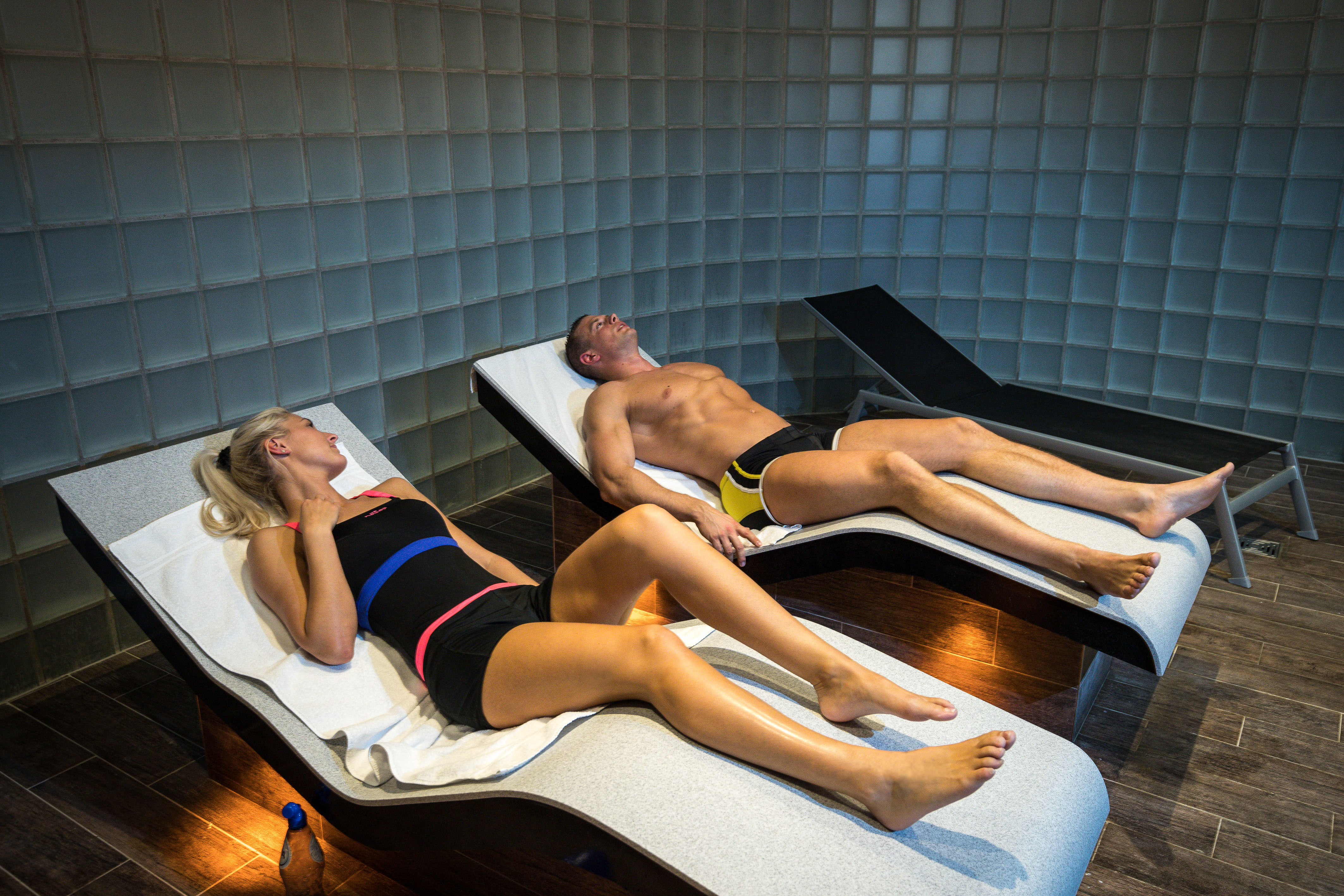 Two people using heated beds in the spa