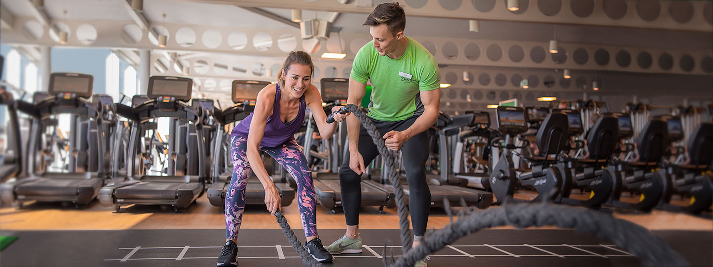 Woman using the battleropes with Personal Trainer at David Lloyd