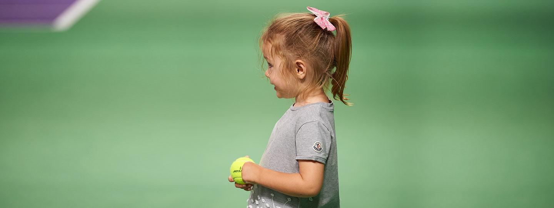 Young girl collecting tennis balls at David Lloyd