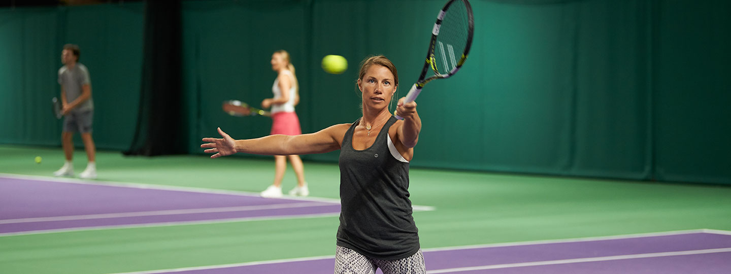 A member serving during game of tennis at David Lloyd