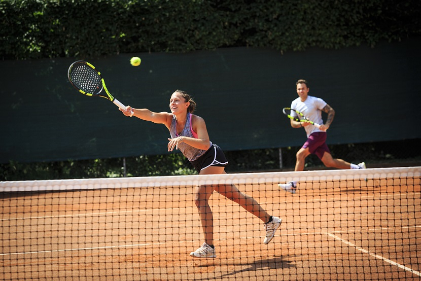 A player hitting a tennis serve on outdoor court