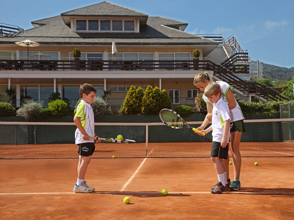 A pair of kids work on their returns with one of our tennis coaches