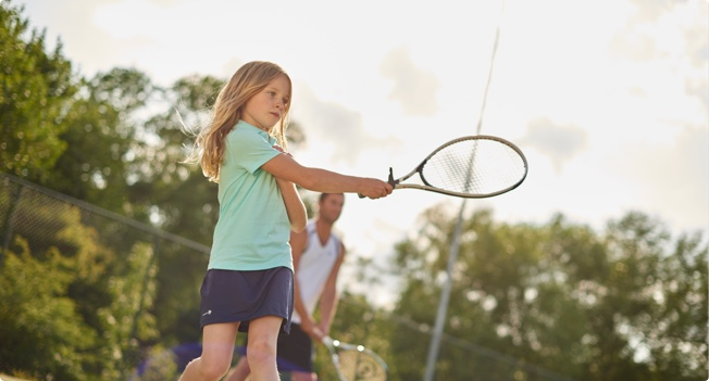 A child member playing tennis