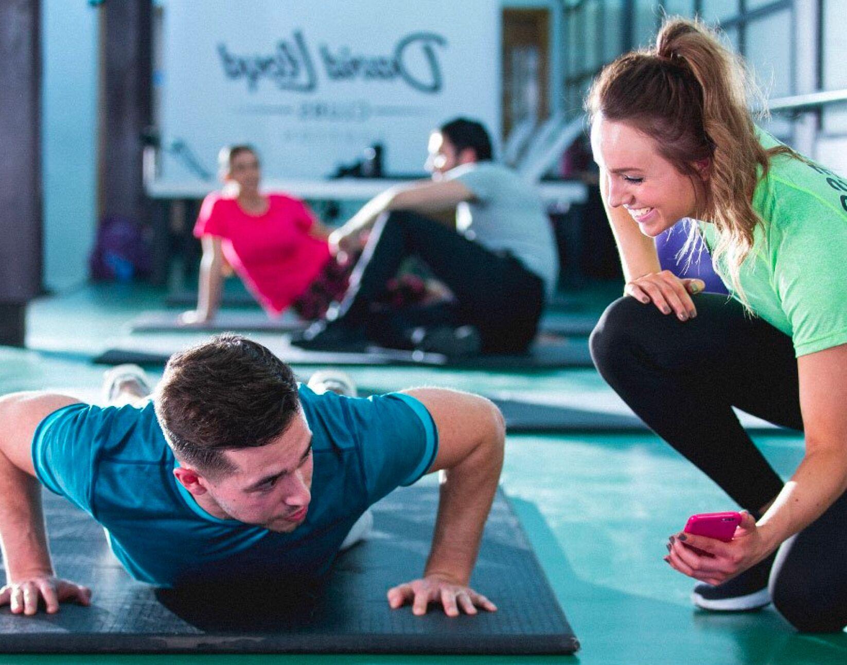 Man doing push ups with Personal Trainer at David Lloyd