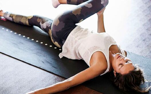 A gym member on a yoga mat stretching