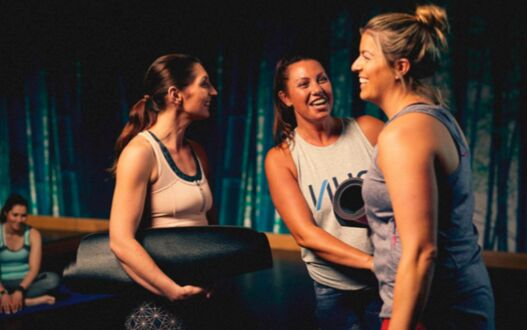 A group of people unwinding after a yoga class in a studio gym