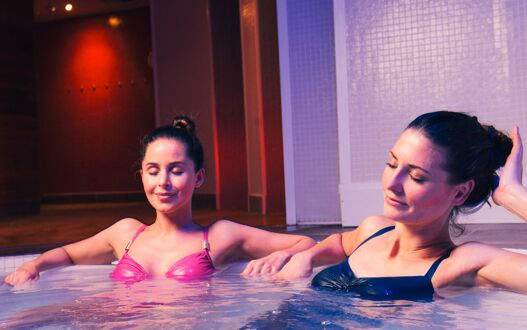 A pair of friends relaxing in the spa pool