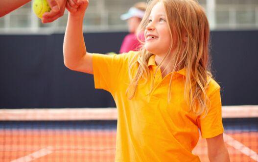 A child enjoying tennis coaching at the club