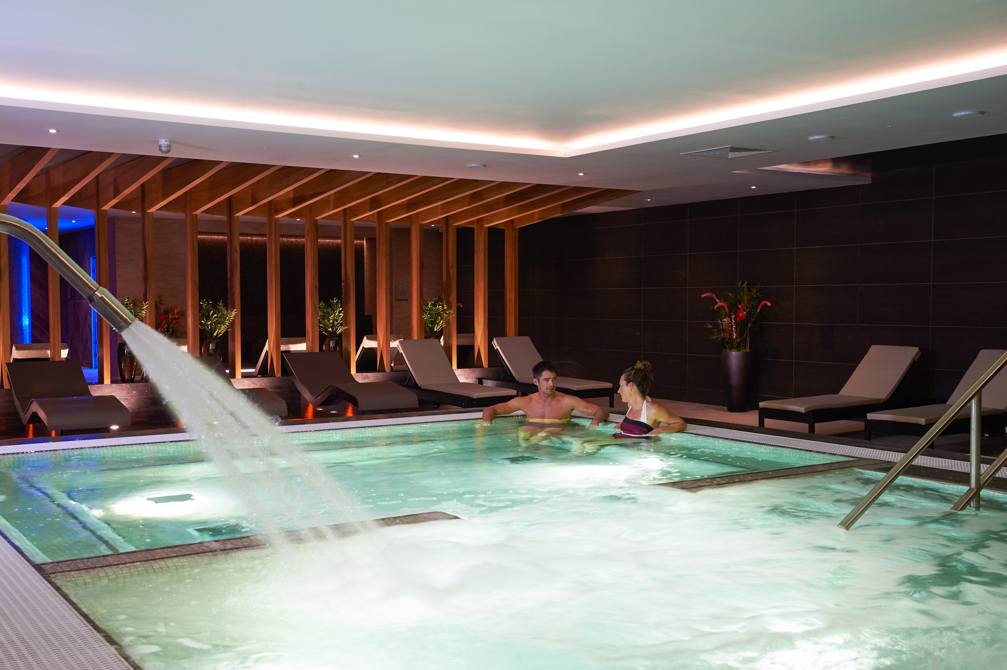 A woman and man reclines blissfully in a spa pool