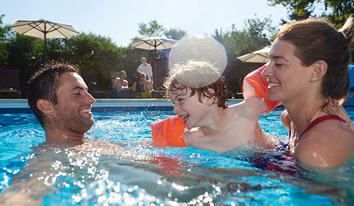 A family enjoying a swim together in the outdoor pool