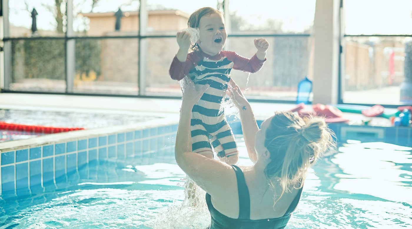 A mother and child playing in the indoor pool