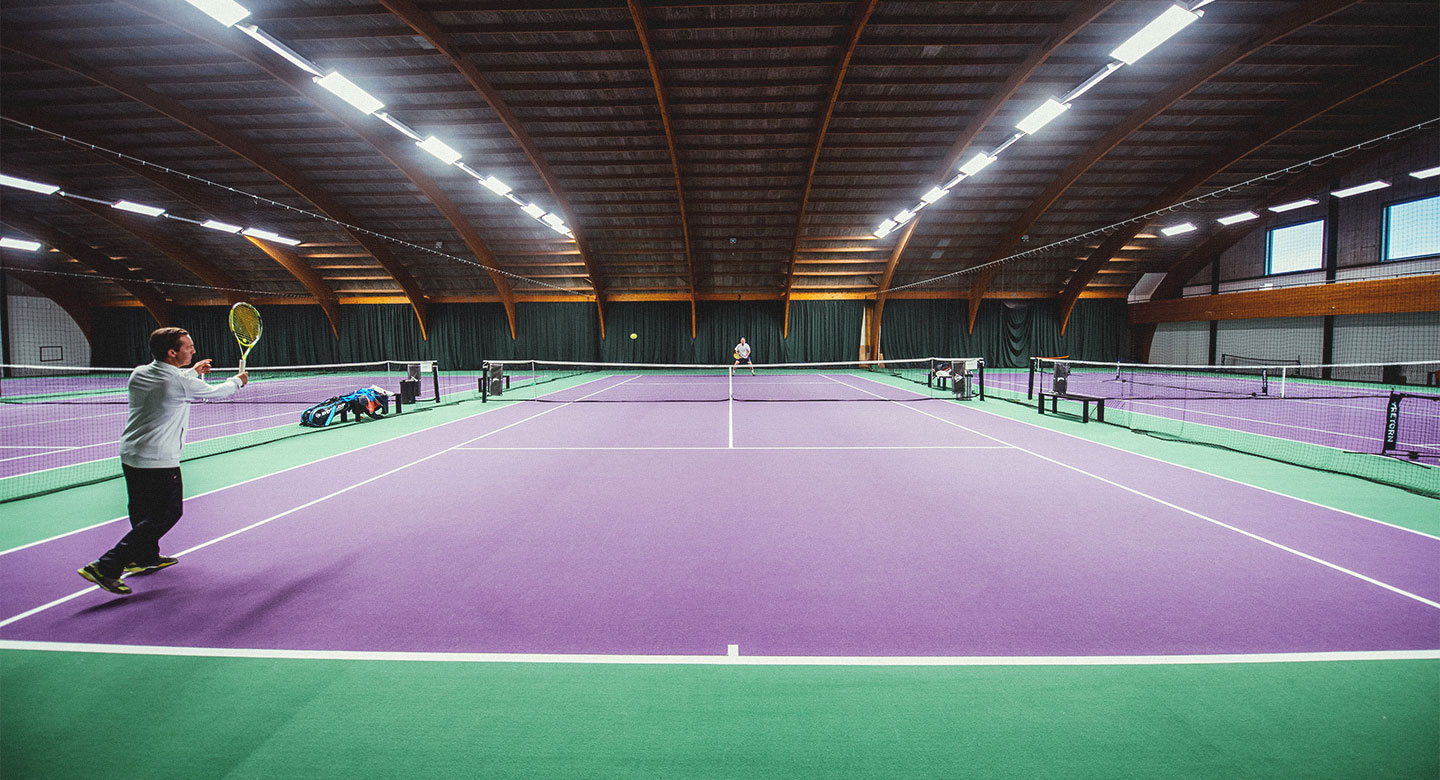 Group playing tennis on indoor court at David Lloyd Antwerp