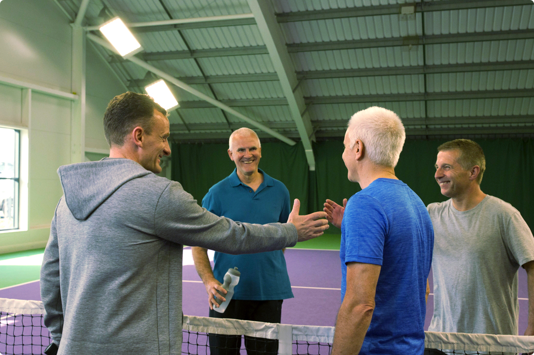 A group of members congratulating each other after a strong game of Tennis