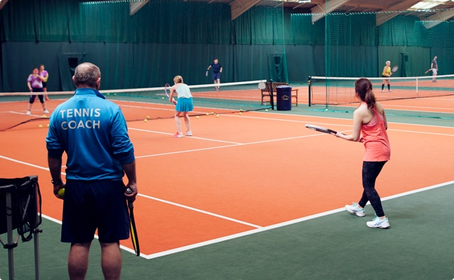 A tennis coach helps a member improve her technique